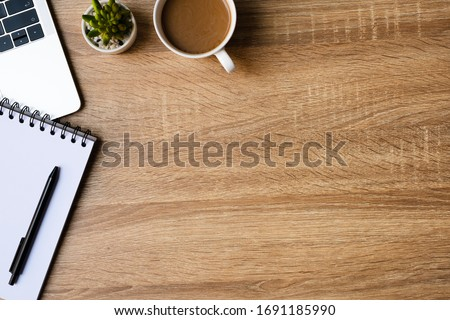 desk office with laptop, blank notepad, coffee cup and pen on wood table. Flat lay top view copy spce. #1691185990