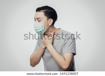 Young Asian Man in hygienic mask suffering sore throat, 2019-nCoV or coronavirus. Airborne respiratory illness such as pm 2.5 fighting and flu. Studio shot isolated on white background. #1691238007