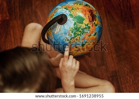Kid is studying the globe. blue. earth day. home school. research. distance learning. continents. our planet. 7 years old child.Coronavirus home school, Royalty-Free Stock Photo #1691238955