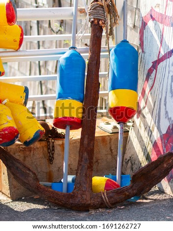 Vertical picture of an old runst anchor with blue, yellow and red lobster buoys in a corner in Portland Maine, USA.