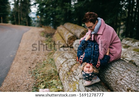 picture of lovely young caucasian female with pretty face, short dark hair, big eyes sits on the felled trees and plays with her child