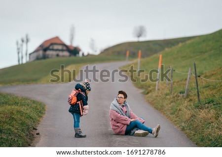 picture of lovely young caucasian female with pretty face, short dark hair, big eyes sits on the ground with her child and rejoices