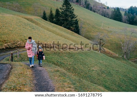 picture of lovely young caucasian female with pretty face, short dark hair, big eyes walks across a field with her child