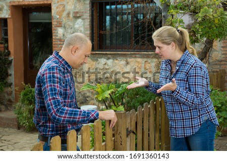 Angry woman quarreling with her male neighbor, talking through wooden fence  #1691360143
