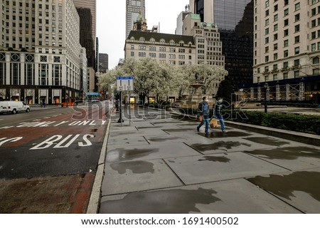 2 people walking through deserted 5th Avenue in NYC during Covid-19 pandemic #1691400502