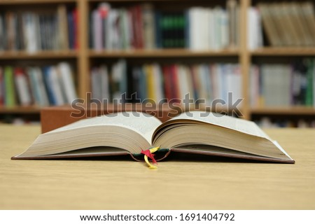 Open book on the table in library #1691404792