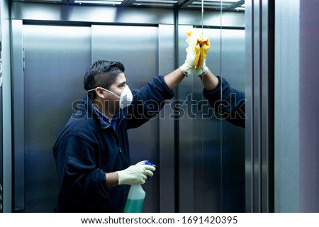 coronavirus. cleaning staff disinfecting elevator to avoid contagion Royalty-Free Stock Photo #1691420395