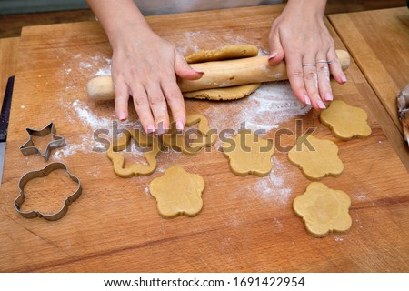 FOOD; woman making homemade biscuits on a kitchen's wooden desktop #1691422954