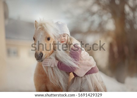 Little girl with palomino miniature horse in winter park #1691429329