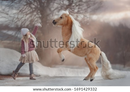 Little girl with palomino miniature horse in winter park #1691429332