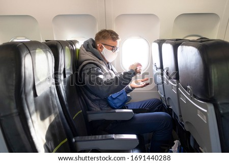 Guy in airplane, young man in glasses, medical protective sterile mask on his face sitting on plane using, apply sanitizer for disinfect hands against coronavirus, virus bacteria. Pandemic covid-19 #1691440288