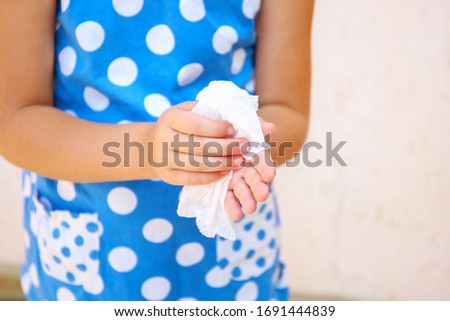 Child wipes his hands with damp cloth. #1691444839
