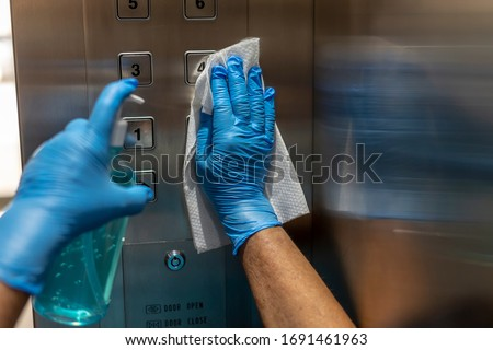 Closeup of old staff hand using wet wipe cleaning an elevator push button control panel with a blue sanitizer bottle.Disinfection,cleanliness and healthcare,Anti Corona virus,COVID-19.Selective focus. #1691461963