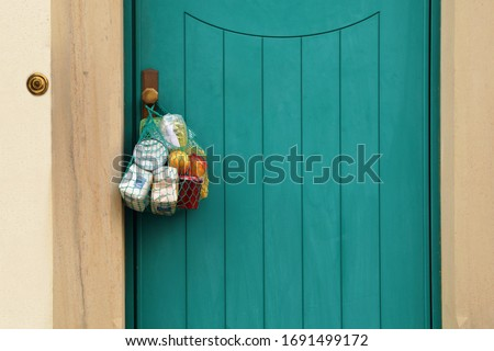 delivery groceries during coronavirus infection Covid-19 quarantine. Shopping bag with Merchandise, goods, food hanging at the front door, neighborhood Assistance. helping of vulnerable people concept #1691499172