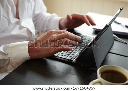 Freelancer man sits at a table and takes notes in a laptop. Concept: freelancer at home behind a laptop screen, remote work in quarantine. Hands and laptop closeup. #1691504959