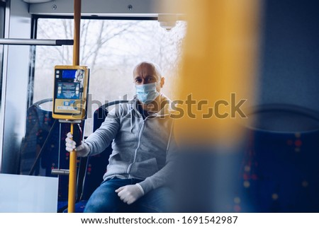 Man in mask and protective gloves traveling by city bus during coronovirus covid-19 pandemic #1691542987