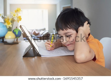 Happy kid having fun watching cartoon on tablet, Child using digital pad searching the ideas on internet for his drawing art homework, Home schooling, Social Distancing, E-learning online education