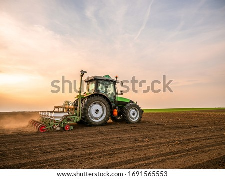 Farmer seeding, sowing crops at field. Sowing is the process of planting seeds in the ground as part of the early spring time agricultural activities. #1691565553