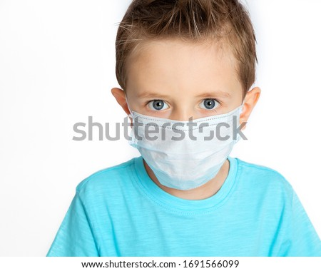 boA boy in a blue t-shirt, wearing a medical mask against a background of coronovirus on a white background. Personal protective equipment against viruses and colds. A child in a mask.  #1691566099