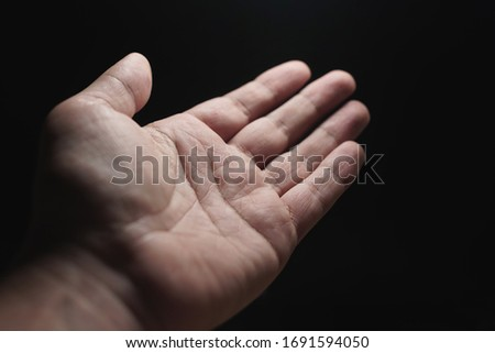 Close-up of a man's hand, palms on a black background. #1691594050