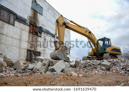 Yellow excavator with bucket at demolition of tall building. Hydraulic machine for demolish. Backhoe destroys concrete of the old structures on construction site Royalty-Free Stock Photo #1691639470
