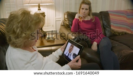 An elderly Caucasian woman and her daughter engaged in a video conference with her doctor via a telehealth or telemed app on a wireless mobile device tablet pc. Royalty-Free Stock Photo #1691640049