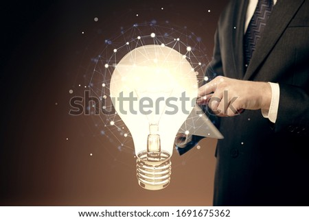Double exposure of man's hands holding and using a digital device and bulb hologram drawing. Idea concept. #1691675362