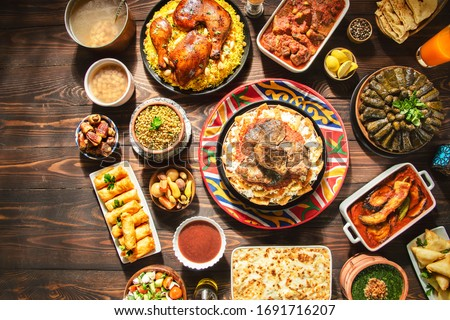 "Arabic Cuisine: Middle Eastern traditional lunch. It;s also Ramadan ""Iftar"" . The Meal eaten by Muslims after sunset during Ramadan. Assorted of Egyptian oriental dishes. Top view with copy space. #1691716207"