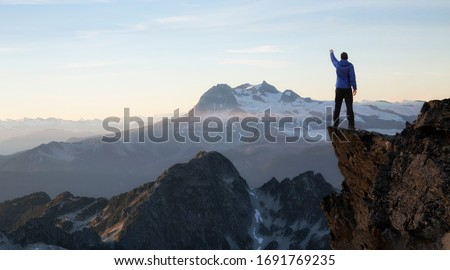 Composite. Adventurous Man Hiker With Hands Up on top of a Steep Rocky Cliff. Sunset or Sunrise. Landscape Taken from British Columbia, Canada. Concept: Adventure, Explore, Hike, Lifestyle #1691769235