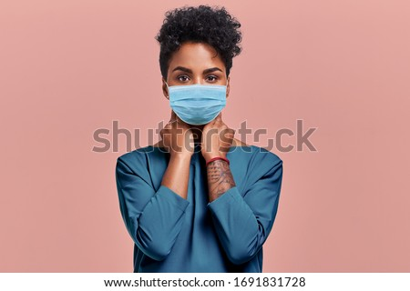 Gorgeous dark skinned young female with Afro hairstyle wearing protective mask against COVID virus, tired of stress and tension, looks confidently at the camera, poses against beige studio background #1691831728
