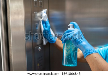 Closeup of old staff hand using wet wipe cleaning an elevator push button control panel with a blue sanitizer bottle.Disinfection,cleanliness and healthcare,Anti Corona virus,COVID-19.Selective focus. Royalty-Free Stock Photo #1691866843