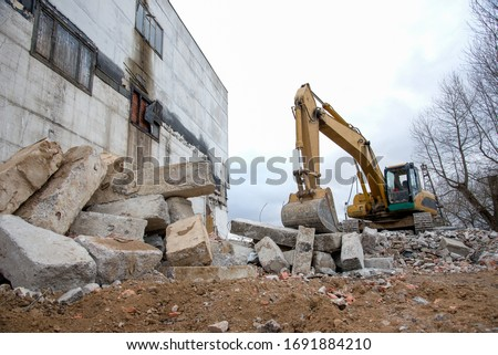 Yellow excavator with bucket at demolition of tall building. Hydraulic machine for demolish. Backhoe destroys concrete of the old structures on construction site Royalty-Free Stock Photo #1691884210