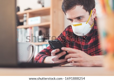 Young man waring face mask is working in the office during corona crisis #1691888254