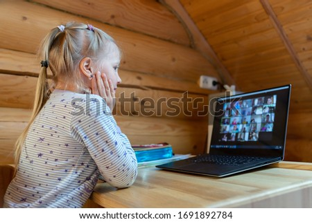 Cute adorable caucasian little blond girl siiting at desk with laptopn during online video chat scholl lesson session with teacher and class. Remote education concept. Self-isloation at quarantine Royalty-Free Stock Photo #1691892784