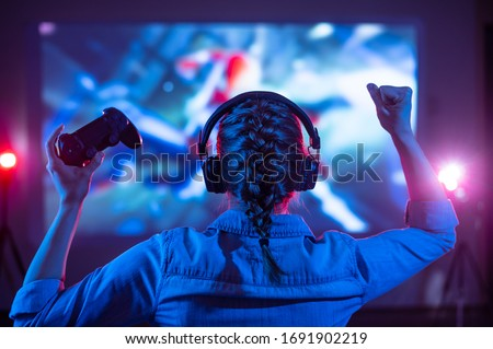 Girl in headphones plays a video game on the big TV screen. Gamer with a joystick. Online gaming with friends, win, prize. Fun entertainment. Teens play adventure games. Back view. Neon lighting