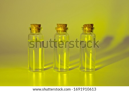 Three glass corked bottles filled with liquid. Background for science and medicine. Virus vaccine. #1691910613