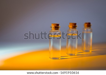 Three glass corked bottles filled with liquid. Background for science and medicine. Virus vaccine. #1691910616