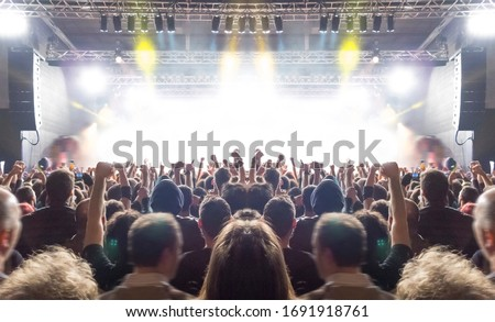 Music festival crowd,concert spectators in front of a bright stage with live music Royalty-Free Stock Photo #1691918761