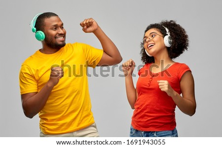 leisure, music and people concept - happy african american couple with headphones dancing over grey background #1691943055