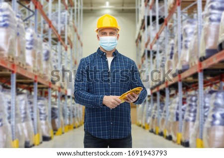 wholesale, logistic, people and export concept - male worker in safety helmet wearing face protective medical mask over warehouse background #1691943793