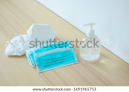 Medical face mask with alcohol sanitizer gel hand wash on wood table for covid-19 Coronavirus prevention concept #1691965753