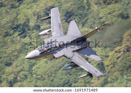 Royal Air Force (RAF) Tornado GR4 strike fighter flying fast  and low level in a mountain valley in Snowdonia North Wales.  #1691971489