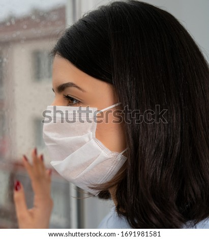 Young woman wearing a mask to protect herself against the coronavirus while going out. Close-up photo. #1691981581