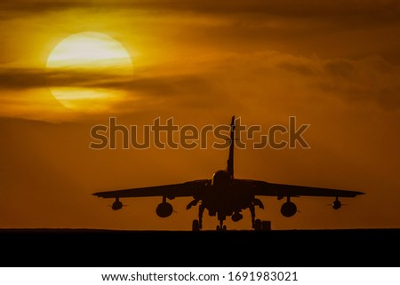 Royal Air Force (RAF ) Tornado GR4 on the runway silhouetted at sunset against a setting sun and orange sky #1691983021