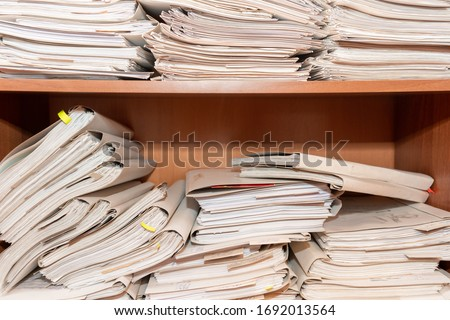 Old paper documents stacked in archive. Documents on the shelves of archive room. Office shelves in the closet full of files #1692013564