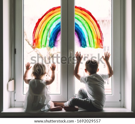 Little children on background of painting rainbow on window. Photo of kids leisure at home. Positive visual support during quarantine Pandemic Coronavirus Covid-19 at home. Family background #1692029557