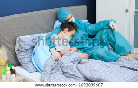 Children and illness COVID-2019 disease concept. Home quarantine at Coronavirus. The coronavirus quarantines a sick boy in a mask and his mother in full protective suit. Royalty-Free Stock Photo #1692039607