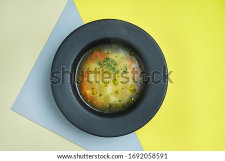 Dietary and healthy chicken stock with vegetables in a black bowl on a colored background. Close up view