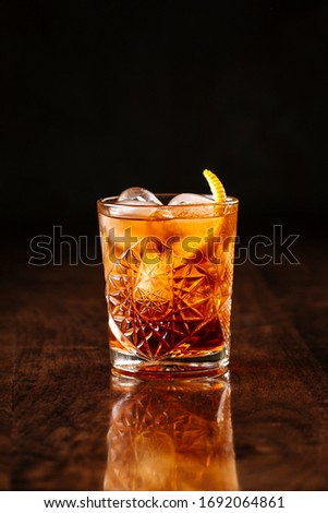 delicious old fashion cocktail in the etched glass with ice and orange slices, dark wooden background, vertical, side view Royalty-Free Stock Photo #1692064861