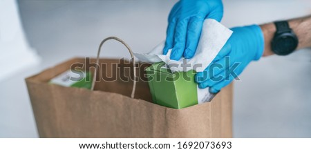 Coronavirus wiping down grocery packages after receiving home delivery wearing gloves, using disinfecting sanitizing wipes to wipe the surfaces clean. Cleaning of COVID-19 virus. #1692073693